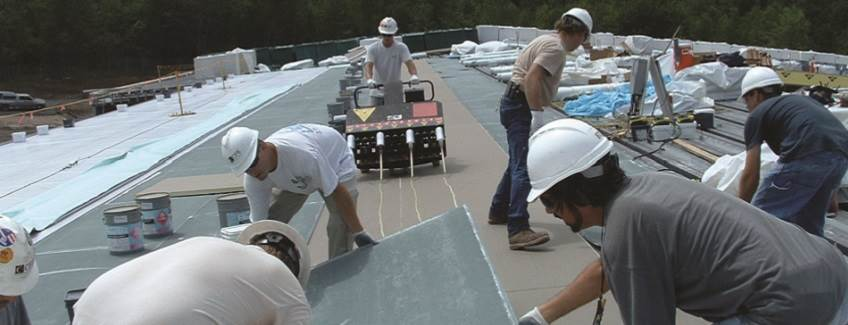 Installing insulation on a commercial roof.